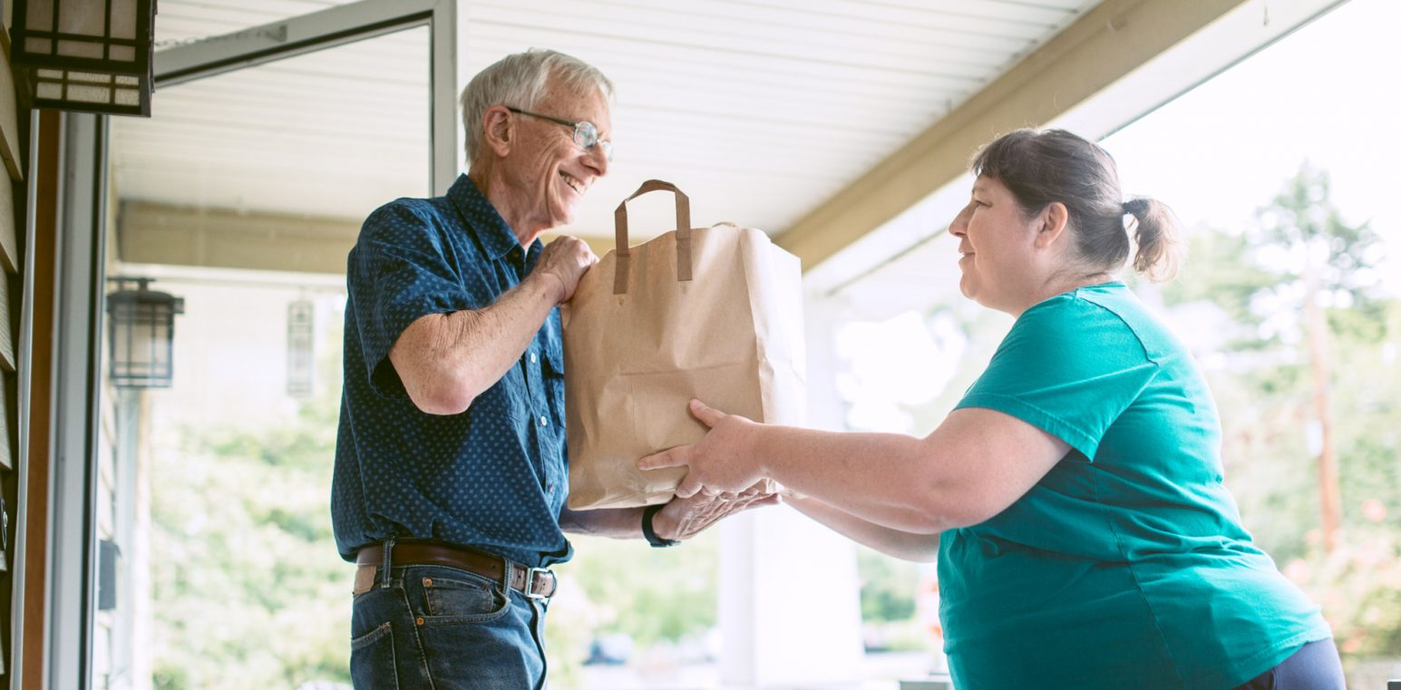 senior male receiving grocery delivery 1545x761